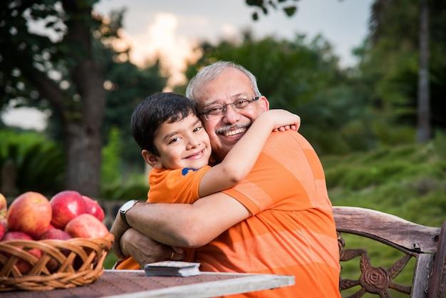Portret szczęśliwych indyjskich azjatyckich dzieci i dziadka siedzącego na krześle ogrodowym