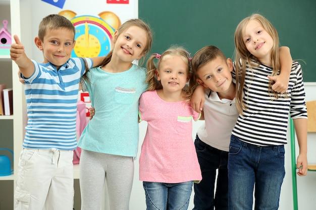 Portret szczęśliwych kolegów z klasy patrząc z przodu w klasie