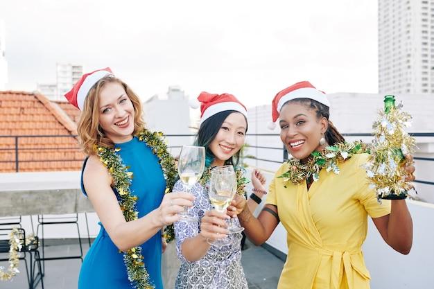 Portret szczęśliwych, ładnych młodych kobiet z blichtrem na szyjach, pijących szampana i świętujących boże narodzenie na dachu