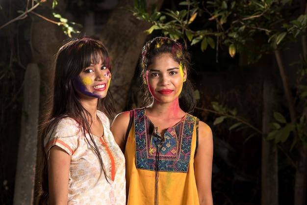 Portret szczęśliwych młodych dziewcząt zabawy z kolorowym proszkiem na festiwalu kolorów holi