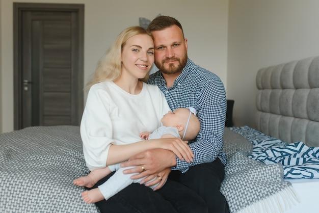 Portret szczęśliwych młodych rodziców z dzieckiem w łóżku w domu