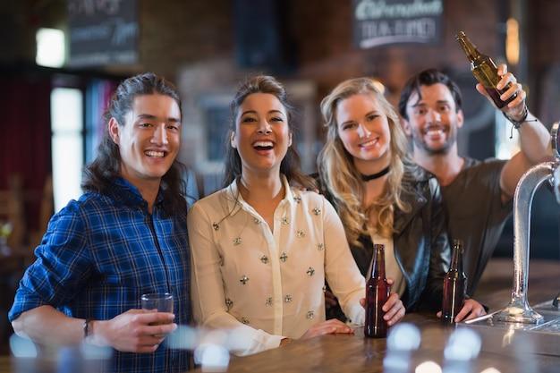 Portret szczęśliwych przyjaciół stojących przy blacie barowym