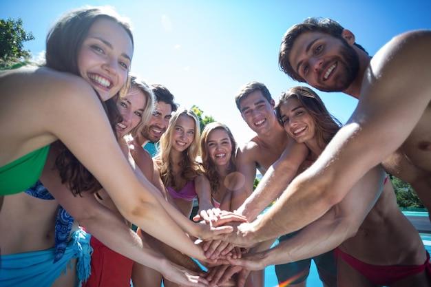 Portret szczęśliwych przyjaciół w strojach kąpielowych, kładąc ręce razem