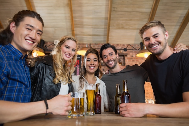 Portret szczęśliwych przyjaciół z szklanką piwa i butelkami