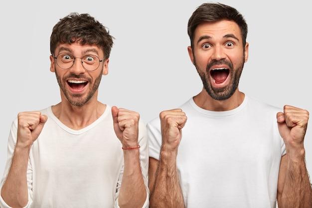 Portret szczęśliwych rozradowanych brodatych facetów zaciskających pięści i radośnie wykrzykujących, wyrażających pewność siebie, radujących się sukcesem, ubrani w białe casualowe koszulki, stoją obok siebie. zwycięska koncepcja