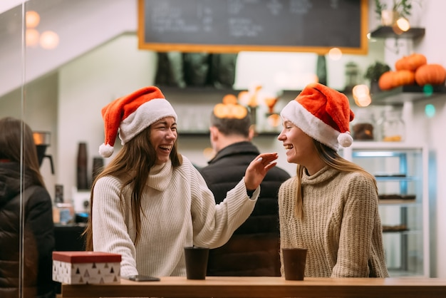 Portret szczęśliwych ślicznych młodych przyjaciół bawiących się w kawiarni