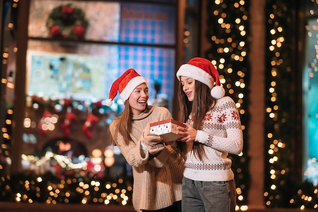 Portret Szczęśliwych ślicznych Młodych Przyjaciół Przytulających Się I Uśmiechających Się Podczas Spaceru W Wigilię Bożego Narodzenia Na Zewnątrz. Darmowe Zdjęcia