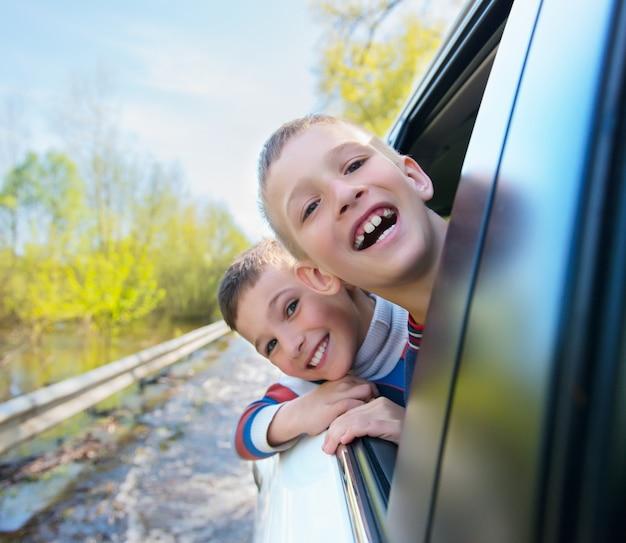 Portret szczęśliwych uśmiechniętych chłopców wygląda przez okno samochodu.