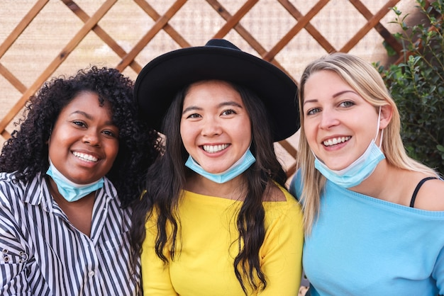 Portret szczęśliwych wielorasowych przyjaciół robiących selfie w plenerze podczas epidemii koronawirusa