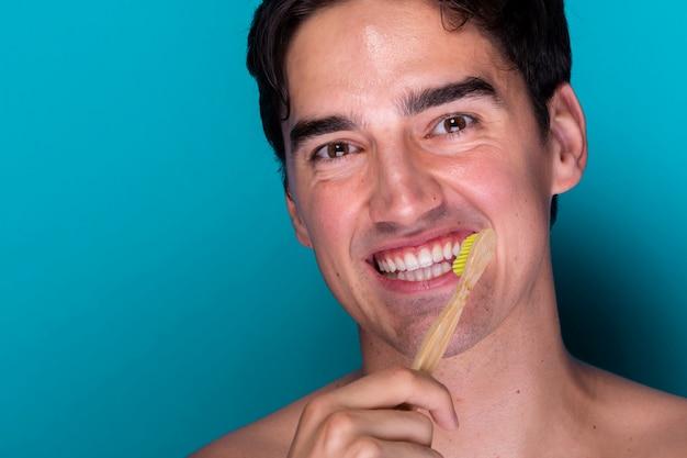 Portret szczotkuje zęby młody człowiek