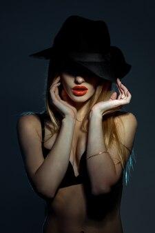 Portret szczupła młoda kobieta w czarnym biustonoszu z czerwonymi ustami na sobie kapelusz z szerokim rondem pozowanie