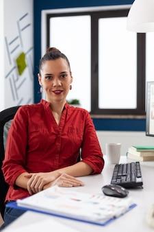 Portret szefa firmy rozpoczynającej działalność, uśmiecha się do kamery podczas wykonywania papierkowej roboty finansowej...
