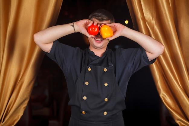 Portret szefa kuchni, który zamknął oczy pomidorem i garścią pieprzu