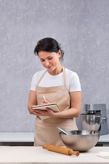 Portret szefa kuchni piszącego przepis w książce kucharskiej. miska kuchenna i wałek do ciasta. rama pionowa.