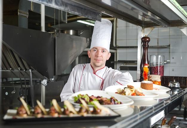 Portret szefa kuchni z gotowanym jedzeniem w kuchni w restauraci.