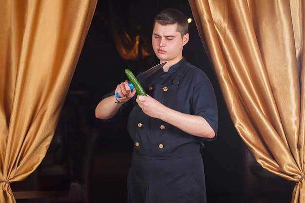 Portret szefa kuchni z nożem i ogórkiem w jego rękach.