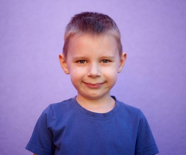 Portret sześcioletniego uśmiechniętego chłopca w niebieskiej koszulce na fioletowym tle