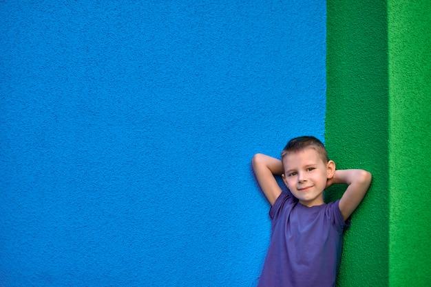 Portret sześcioletniego uśmiechniętego chłopca w niebieskiej koszulce na tle ściany zieleni i błękitu