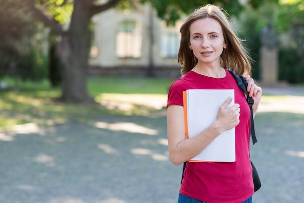 Portret szkolna dziewczyna z książkami w parku