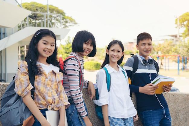Portret szkolni dzieciaki z plecakami uśmiecha się stać w korytarzu szkoły podstawowej