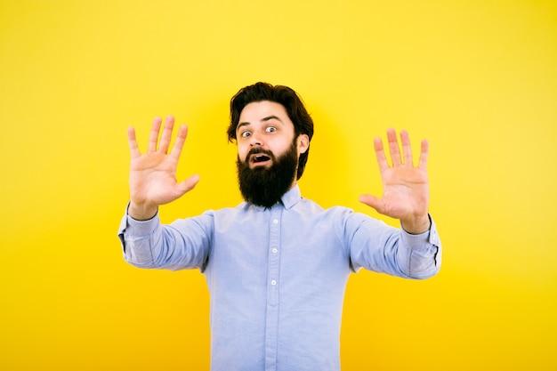 Portret szoku brodaty mężczyzna trzyma ręce w górze. zdziwiony facet w przypadkowej koszuli na żółtym tle.