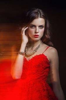 Portret sztuki niewyraźne kolor dziewczyny na ciemnym tle. moda kobieta z pięknym makijażem i lekką letnią sukienką. zmysłowy obraz przetargu dziewczyny w ruchu. portret studyjny
