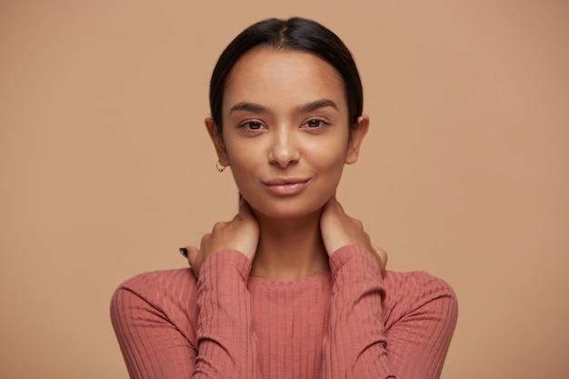 Portret tajemniczej, intrygującej, pięknej zadowolonej kobiety o ciemnych włosach zaczesanych do tyłu, dotykających szyi