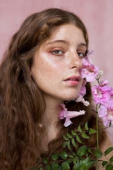 Portret tajemniczej piegowatej kobiety trzymającej różowy kwiat