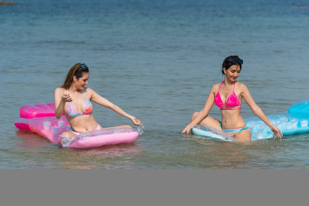 Portret tajskich kobiet pozujących na kolorowych dmuchańcach na wodzie na plaży