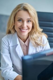 Portret talii w górę, pełna humoru, urocza blondynka w średnim wieku, lekarka z komputerem patrzącym przed nią