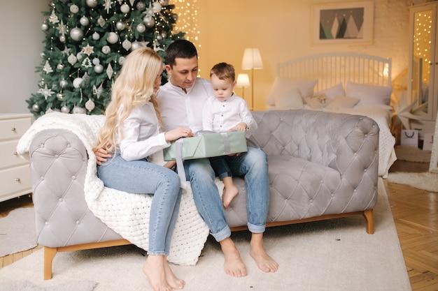 Portret taty, mamy i syna siedzących na podłodze w domu w pobliżu choinki, wszyscy uśmiechają się. dżinsowe i białe koszule. świąteczna rodzina. szczęście.