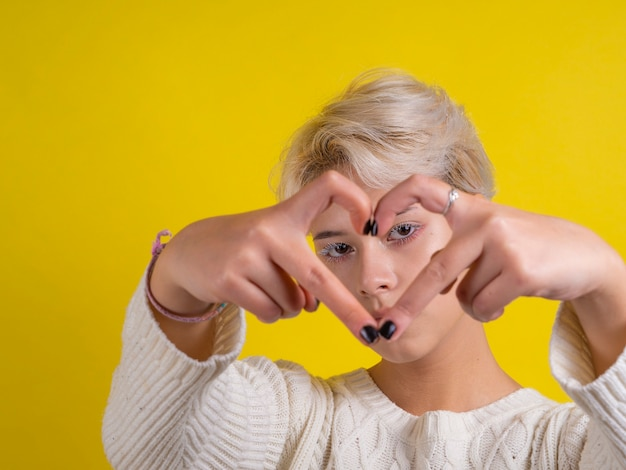 Portret teen girl podejmowania kształt serca rękami