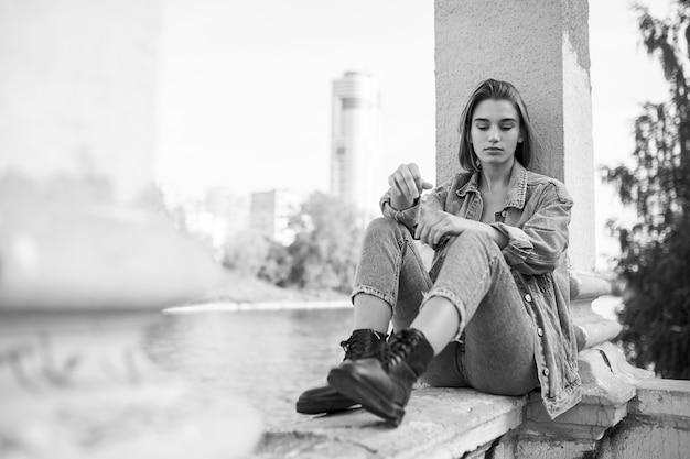 Portret tęskni zadumana nastolatka ubrana w drelich i buty, siedząca. widok poziomy.