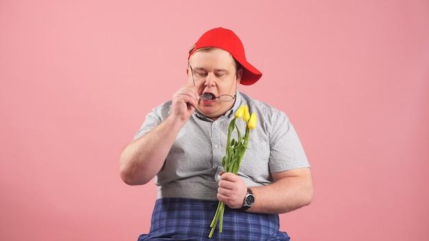 Portret tłuściuchny młody człowiek w szkłach z bukietem kwiaty na odosobnionym różowym tle