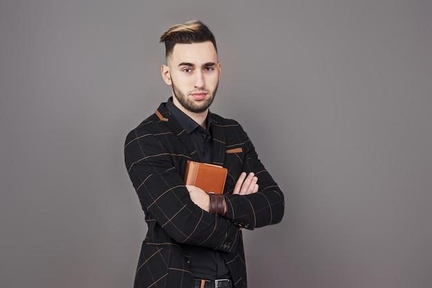Portret toothy przystojny brodaty mężczyzna z książką na rękach