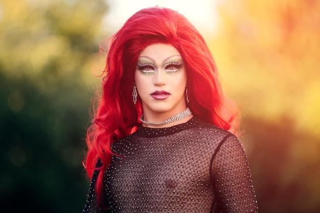 Portret transpłciowej kobiety, transpłciowej kobiety w czerwonej peruce, patrzącej w kamerę, na niewyraźnym tle drzew.