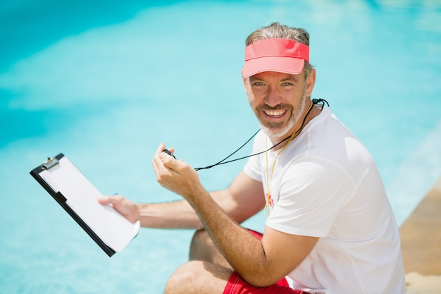 Portret trenera pływania trzymając stoper i schowek w pobliżu basenu