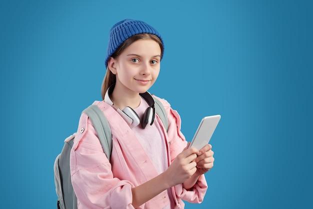 Portret treści nastolatka w kapeluszu czapka na sobie tornister za pomocą aplikacji mobilnej