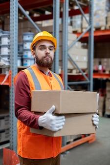Portret treści pewny siebie młody depozytor w kasku i kamizelce odblaskowej stojący z pudełkami na ramie magazynu