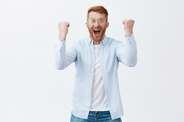 Portret triumfującego szczęśliwego kaukaskiego mężczyzny z rudymi włosami i włosiem w okularach krzyczącego z sukcesu i pozytywnych emocji podnoszących pięści, aby świętować zwycięstwo