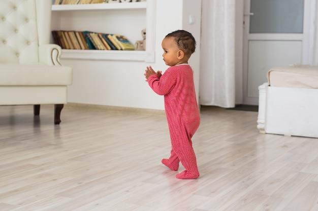 Portret trochę african american chłopca, grając w pomieszczeniach.