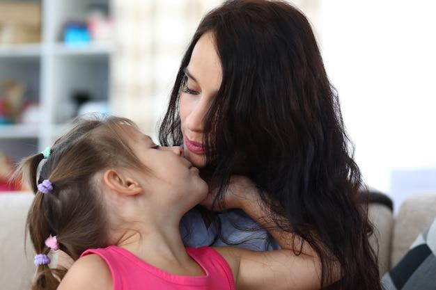Portret troskliwej mamusi i zadowolonego dziecka spędzającego razem zabawny czas w domu. urocza matka całuje szczęśliwą córkę. koncepcja dzieciństwa i rodzicielstwa