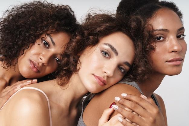 Portret trzech atrakcyjnych, wieloetnicznych kobiet przytulających się do siebie