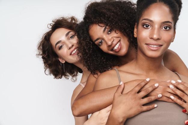 Portret trzech atrakcyjnych, wieloetnicznych kobiet, uśmiechniętych i przytulających się razem