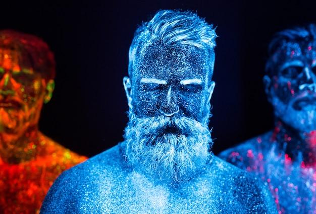 Portret trzech brodatych mężczyzn pomalowanych we fluorescencyjne proszki.