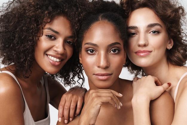 Portret trzech brunetek wielorasowych kobiet stojących razem i patrzących na kamerę