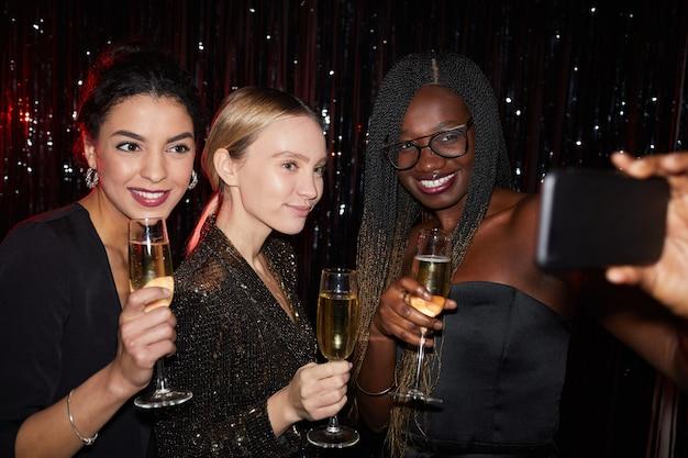 Portret trzech eleganckich młodych kobiet trzymających kieliszki do szampana i uśmiechających się podczas robienia zdjęć selfie na imprezie, strzał z lampą błyskową