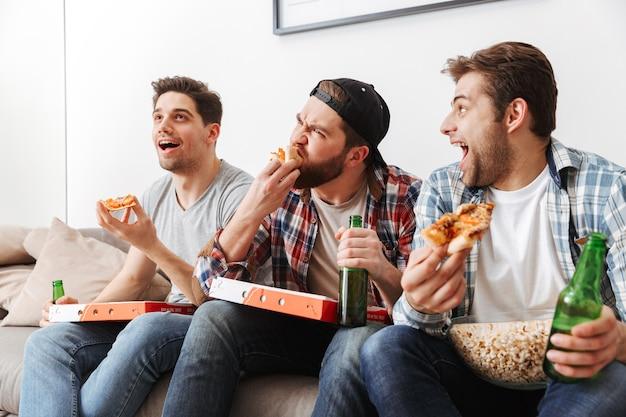 Portret trzech głodnych mężczyzn jedzących pizzę i pijących piwo, jednocześnie kibicujących drużynie piłkarskiej w domu