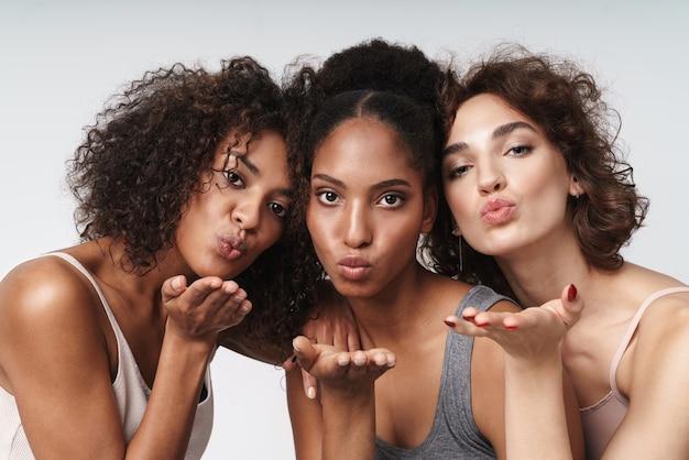 Portret trzech ładnych wielorasowych kobiet stojących razem i dmuchających powietrzem pocałunkiem przed kamerą