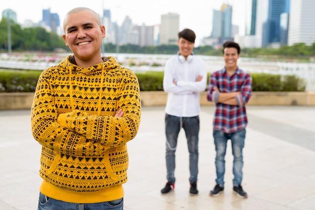 Portret trzech młodych mężczyzn azjatyckich razem relaks w parku w bangkoku w tajlandii